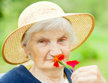 elderly woman smelling some flowers